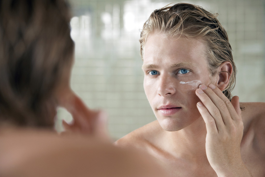 Closeup of handsome young man applying facial cream in front of