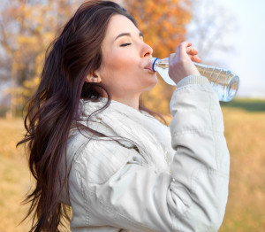 Young woman drinking water in the autumn park